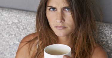 Cropped shot of an attractive young woman looking miserable while drinking coffee in bed